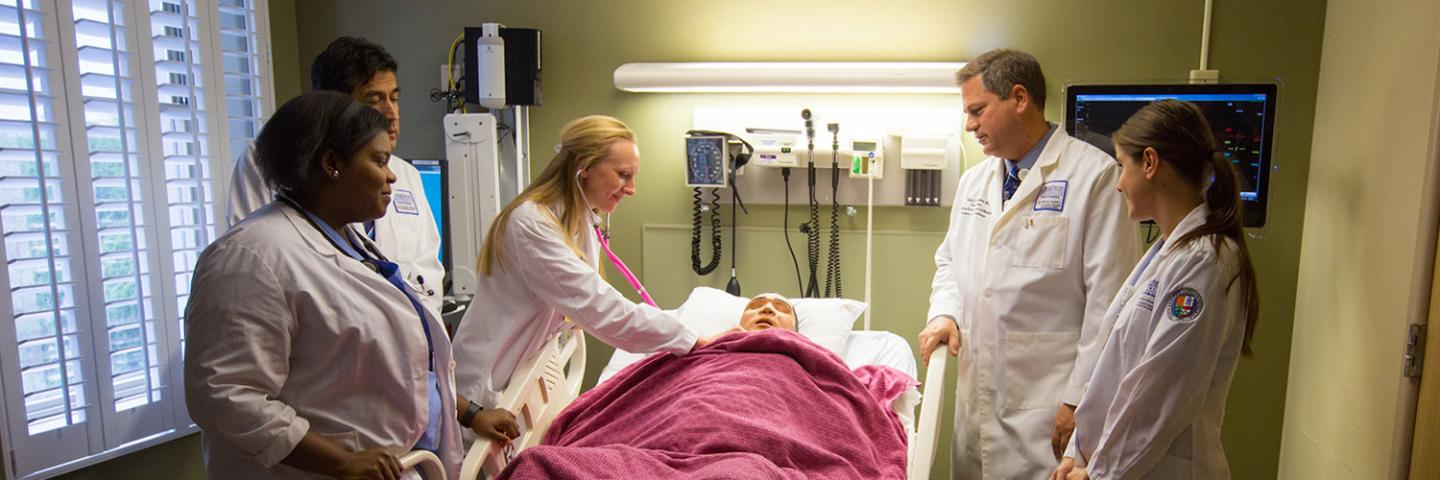 Students in clinical setting with faculty member